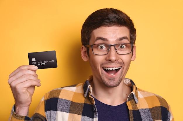 Ritratto del primo piano dell'uomo uscito in vetri e vestiti casuali che mostrano la carta di credito di plastica della banca su colore giallo