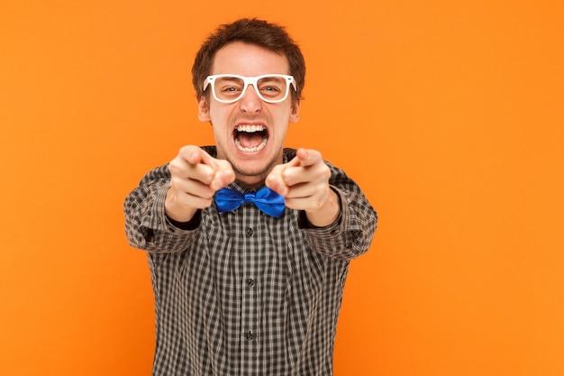 Ritratto del primo piano che esprime impiegato che indica le dita alla macchina fotografica e che sembra arrabbiato. colpo dello studio. isolato su sfondo arancione