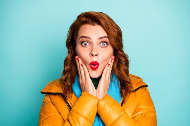 Il ritratto del primo piano dell'acquirente dipendente dalla bocca aperta della signora divertente guarda i prezzi bassi del venerdì nero indossa il dolcevita verde della sciarpa blu del soprabito giallo.