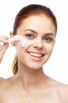 Ritratto del primo piano della ragazza che applica la maschera facciale su fondo bianco