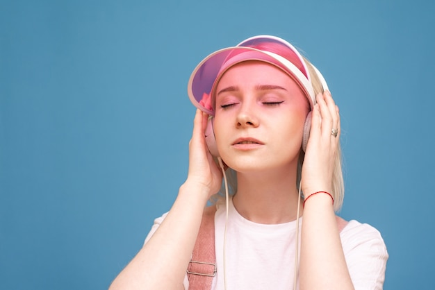Closeup ritratto di una ragazza in una maglietta bianca e un berretto rosa, ascolta la musica nelle sue cuffie con gli occhi chiusi sul blu
