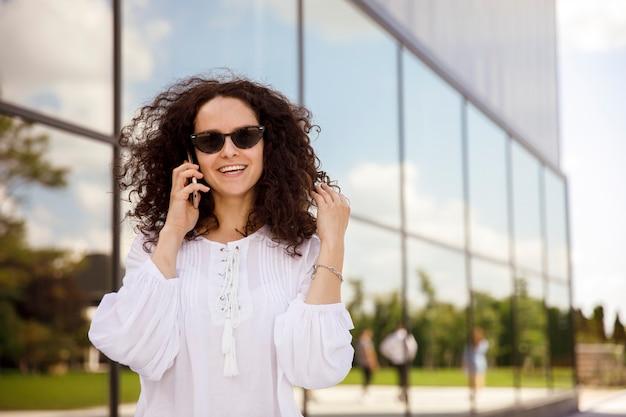 Closeup ritratto di una ragazza con i capelli ricci in occhiali da sole, parlando al cellulare, contro un edificio con sfondo della finestra.
