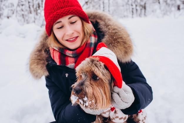 Ritratto del primo piano di una ragazza con un cane nella foresta di inverno, cane in una tuta rossa, ragazza in un cappello lavorato a maglia rosso