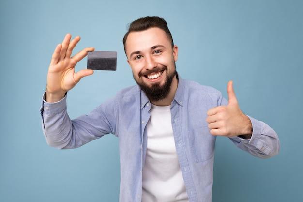 Ritratto del primo piano di un giovane barbuto bruna sorridente di bell'aspetto che indossa una camicia blu elegante