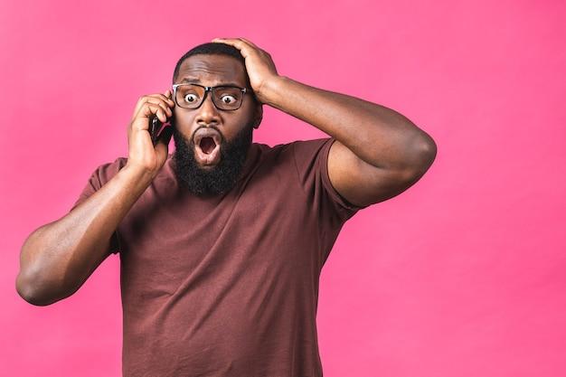 Ritratto del primo piano dell'uomo di colore afroamericano bello, bocca scioccata, sorpresa, spalancata, utilizzando il telefono cellulare, isolato su sfondo rosa. emozioni umane negative.