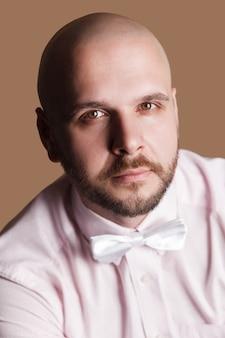 Ritratto del primo piano dell'uomo calvo barbuto bello in camicia rosa chiaro e fiocco bianco, che guarda l'obbiettivo con la faccia seria. girato in studio al coperto, isolato su sfondo marrone.