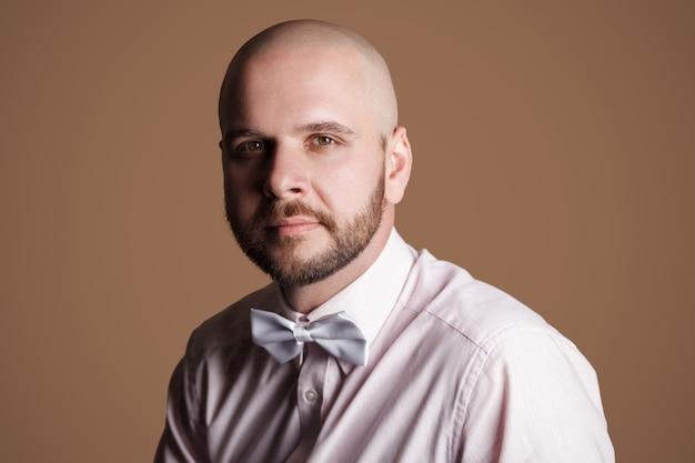 Ritratto del primo piano dell'uomo calvo barbuto bello in camicia rosa chiaro e fiocco bianco, seduto sulla sedia e che guarda l'obbiettivo con viso fiducioso soddisfatto. foto in studio al coperto, isolata su sfondo marrone