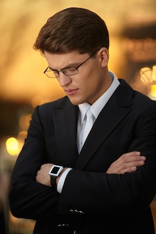 Closeup ritratto di un bell'uomo d'affari in posa con le braccia incrociate in occhiali e abito nero, indossa l'orologio in mano.