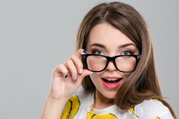 Ritratto del primo piano di un'adolescente femminile felice che guarda l'obbiettivo isolato su uno sfondo bianco