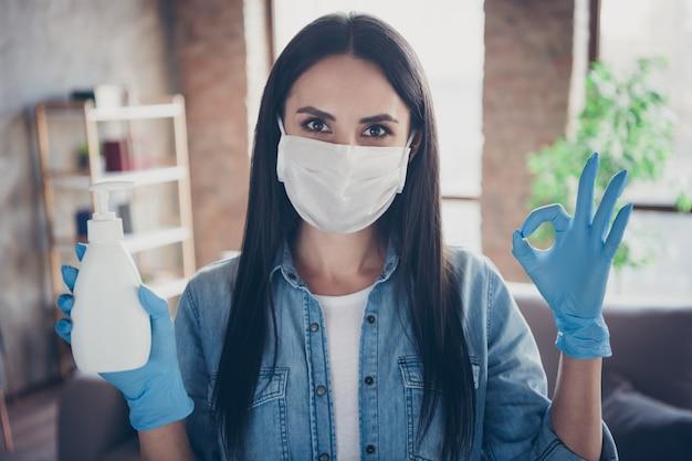 Closeup ritratto di lei bella attraente sana fiduciosa ragazza bruna che tiene in mano disinfezione sapone liquido sicurezza mostrando oksign in moderno loft mattone casa industriale appartamento