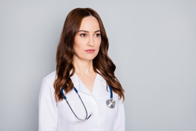 Closeup ritratto di lei lei bella attraente piuttosto contenuto serio esperto medico rosso foxy zenzero ondulato terapista indossa camice bianco isolato su sfondo grigio colore pastello