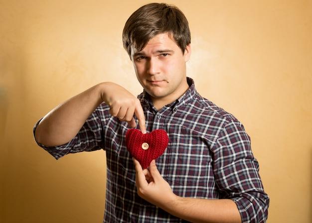 Ritratto del primo piano dell'uomo dei pantaloni a vita bassa che indica sul cuore tricottato rosso
