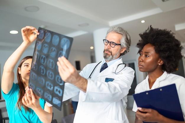 Ritratto del primo piano del personale sanitario di medici intellettuali con camice bianco, guardando l'immagine radiografica dei raggi x dei polmoni, tac, risonanza magnetica, fondo isolato della clinica ospedaliera. reparto di radiologia