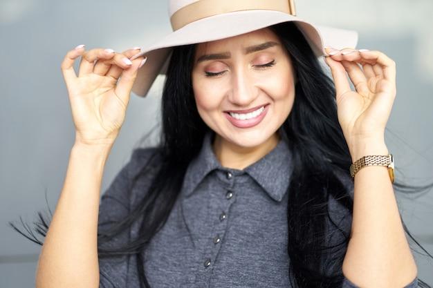 Ragazza castana attraente allegra del ritratto del primo piano con gli occhi chiusi che portano tenuta grigia alla moda del vestito e cappello alla moda. focalizzazione morbida.