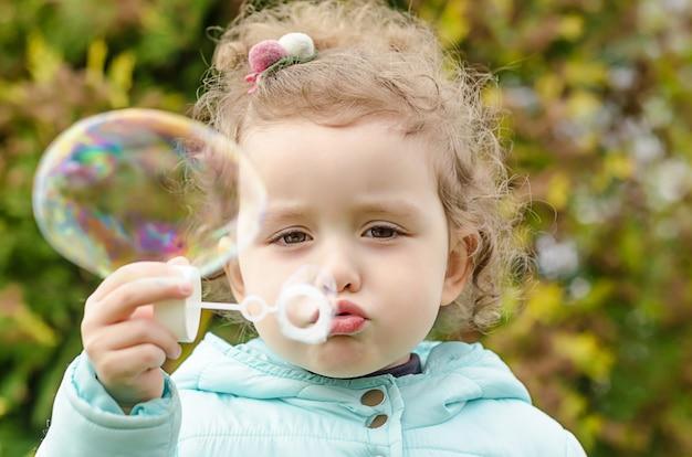 Ritratto del primo piano di piccola bella ragazza che spegne le bolle di sapone. il tempo libero dei bambini. divertenti giochi all'aperto
