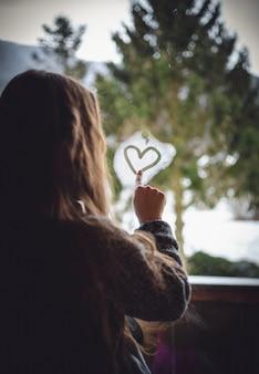 Ritratto del primo piano della bambina che disegna il cuore sulla finestra congelata