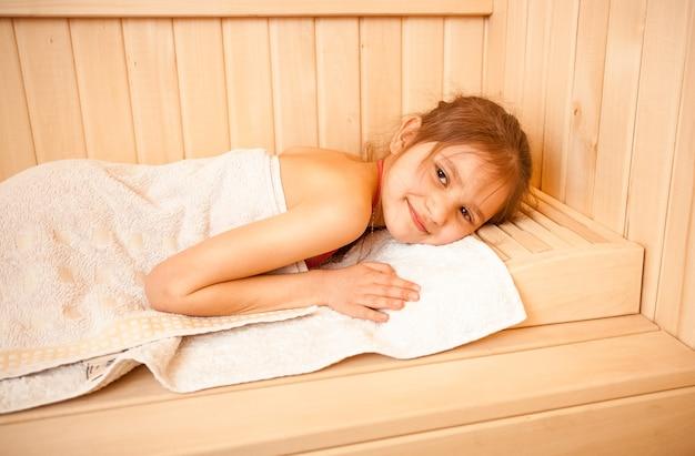 Ritratto del primo piano della bambina che si trova sull'asciugamano alla sauna