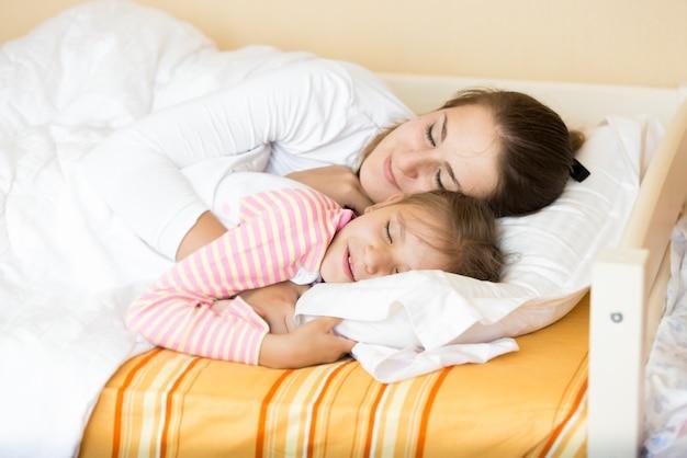 Ritratto del primo piano della bambina che dorme con la madre sul letto