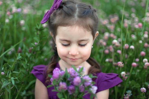 Closeup ritratto di bambina con grandi occhi belli e con bouquet di fiori di campo