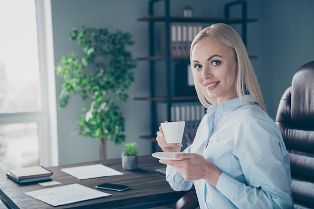 Ritratto del primo piano della bella ragazza esperta che beve caffè sul posto di lavoro