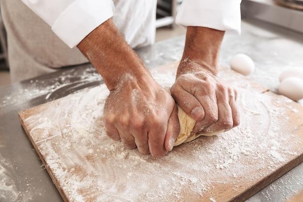 Ritratto del primo piano delle mani maschii che producono pasta per la pagnotta, sul tavolo al forno o in cucina