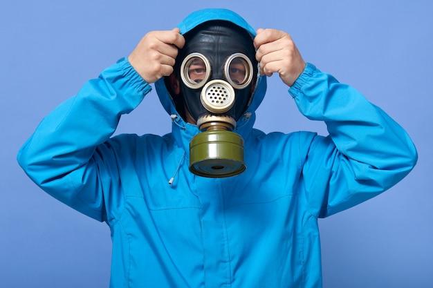 Ritratto del primo piano dell'uomo che mette sul cappuccio, respiratore d'uso maschio sul suo fronte e uniforme
