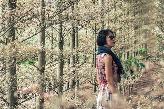 Ritratto del primo piano della donna matura asiatica moderna alla foresta
