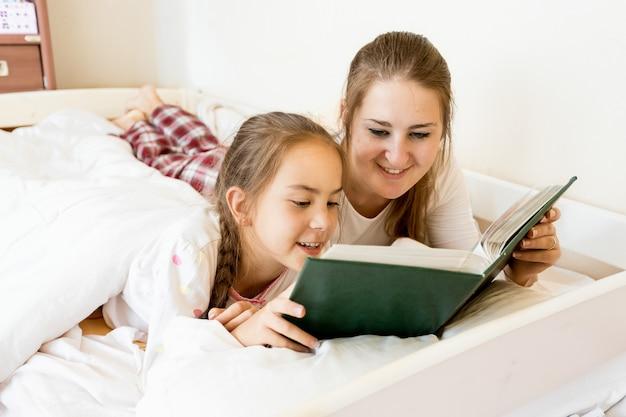 Ritratto del primo piano della madre sdraiata con la figlia sul letto e leggendo un libro