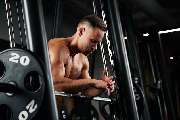 Closeup ritratto di un uomo muscoloso allenamento con bilanciere in palestra. uomo atletico culturista brutale con six pack, addominali perfetti, spalle, bicipiti, tricipiti e petto.