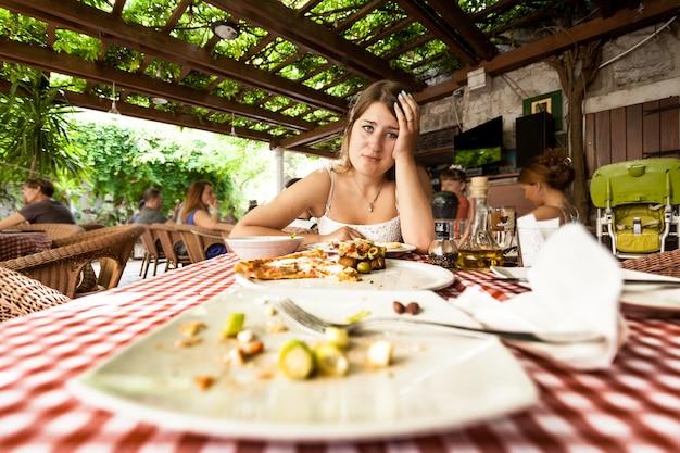 Ritratto del primo piano della donna che mangia troppo guardando i piatti vuoti sul tavolo al ristorante