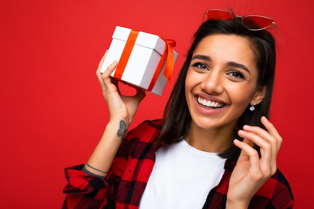 Foto ritratto del primo piano di bella giovane donna brunet sorridente felice isolata sulla parete rossa del fondo