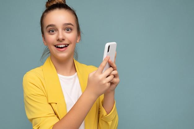 Ritratto del primo piano foto scattata di attraente giovane studentessa di bell'aspetto positivo che indossa casual