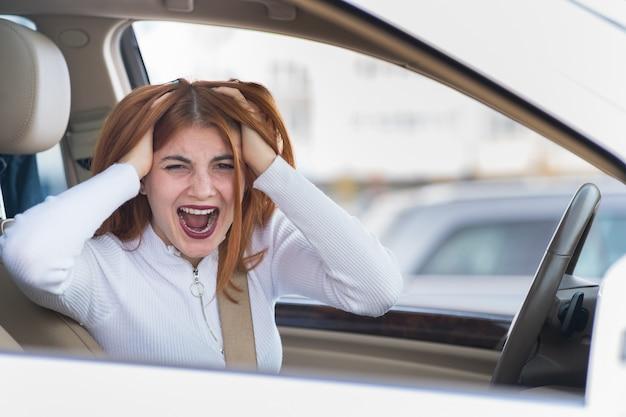 Ritratto del primo piano della donna aggressiva arrabbiata dispiaciuta scocciata che conduce un'automobile che grida a qualcuno. concetto di espressione umana negativa