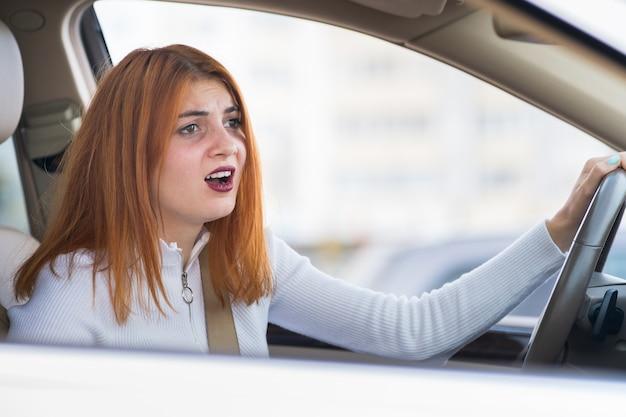 Ritratto del primo piano della donna aggressiva arrabbiata dispiaciuta scocciata che conduce un'automobile che grida a qualcuno. concetto di espressione umana negativa.