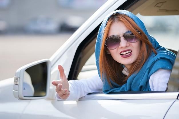 Ritratto del primo piano della donna aggressiva arrabbiata dispiaciuta scocciata che conduce un'automobile che grida a qualcuno con il pugno della mano su. concetto di espressione umana negativa