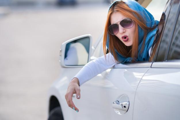 Ritratto del primo piano della donna aggressiva arrabbiata dispiaciuta scocciata che conduce un'automobile che grida a qualcuno con il pugno della mano su. concetto di espressione umana negativa.