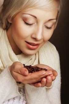 Il ritratto del primo piano della ragazza bionda graziosa tiene i chicchi di caffè tostati caldi nelle mani