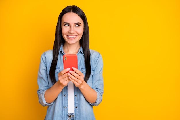 Il ritratto del primo piano di una ragazza piuttosto curiosa che utilizza lo smartphone sembra uno spazio vuoto