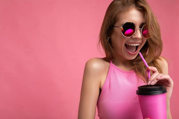 Closeup ritratto di bella giovane donna bionda positiva che indossa top rosa e occhiali da sole colorati