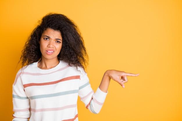 Closeup ritratto di triste ragazza disgustata che punta il dito per copiare lo spazio