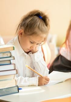 Ritratto del primo piano dell'esercizio di scrittura della ragazza triste nel libro di testo a scuola