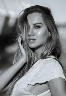 Ritratto del primo piano di una modella seducente con una pelle perfetta e lunghi capelli biondi. tonificazione in bianco e nero