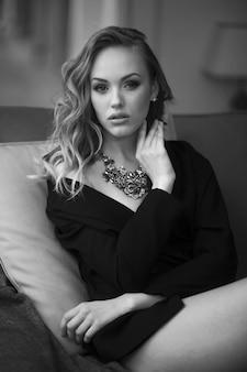 Closeup ritratto di una giovane donna sexy in abito classico nero, sensuale guardando la telecamera