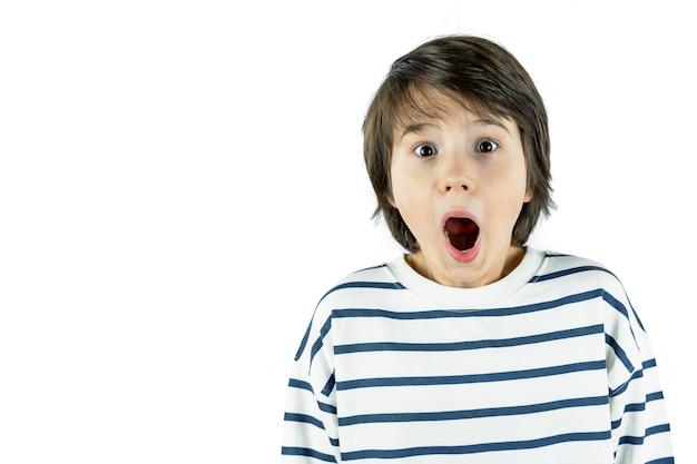 Ritratto del primo piano del giovane ragazzo sorpreso spaventoso scioccato di nove anni