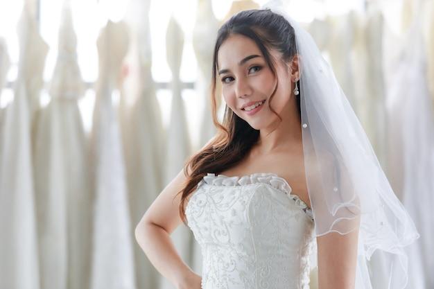 Colpo del ritratto del primo piano della sposa asiatica giovane bella felice capelli lunghi in abito da sposa bianco con velo trasparente in piedi sorridente sguardo alla macchina fotografica in spogliatoio pieno di abiti in sfondo sfocato.