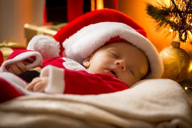 Ritratto del primo piano del neonato addormentato in cappello di babbo natale in soggiorno