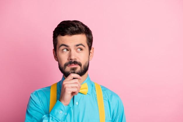 Ritratto del primo piano del ragazzo barbuto intelligente intelligente che crea soluzione