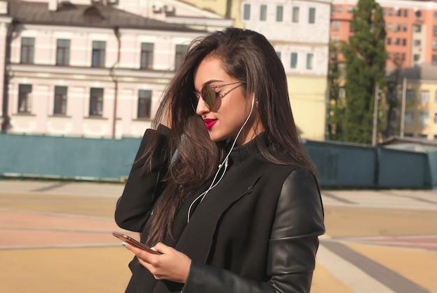 Closeup ritratto di donna bruna sorridente che guarda video sul telefono cellulare, in piedi per strada