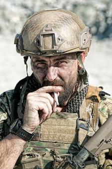 Ritratto del primo piano del soldato di fumo nel deserto tra le rocce