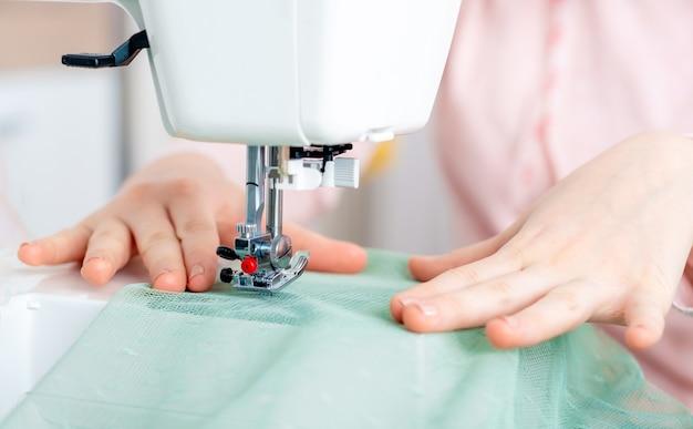 Ritratto del primo piano di una ragazza adolescente che utilizza una macchina da cucire con precisione